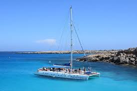 catamaran in turquiose water against rocky shore