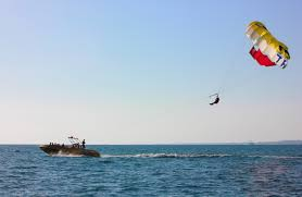 parasail being pulled by boat against blue sky