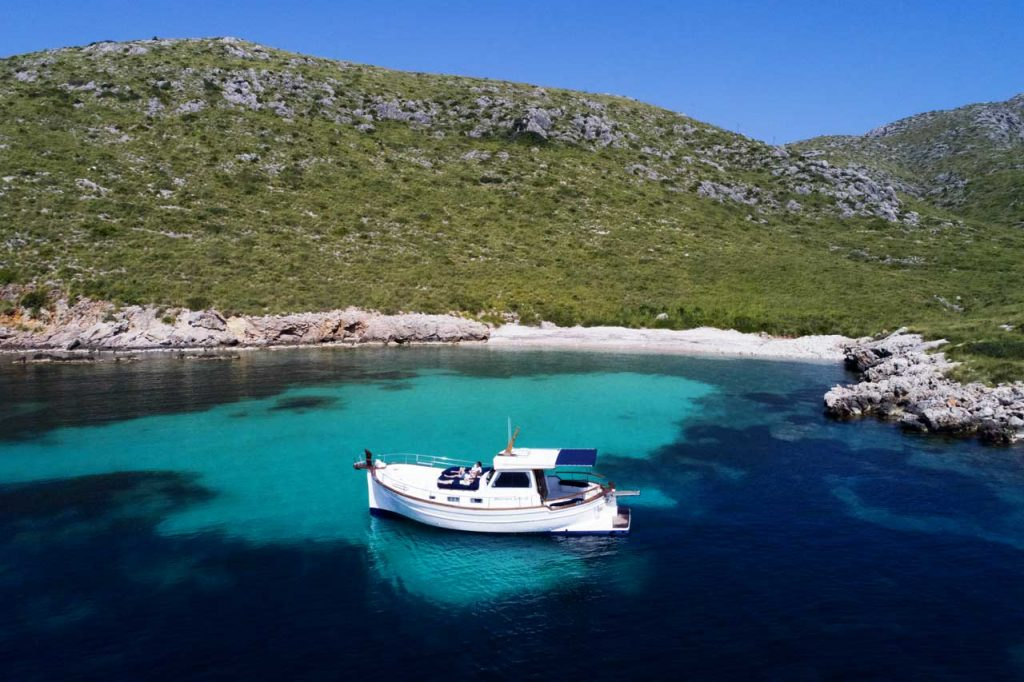 llaüt-boat in a secluded bay with turquoise and deep-blue water near Puerto Pollensa