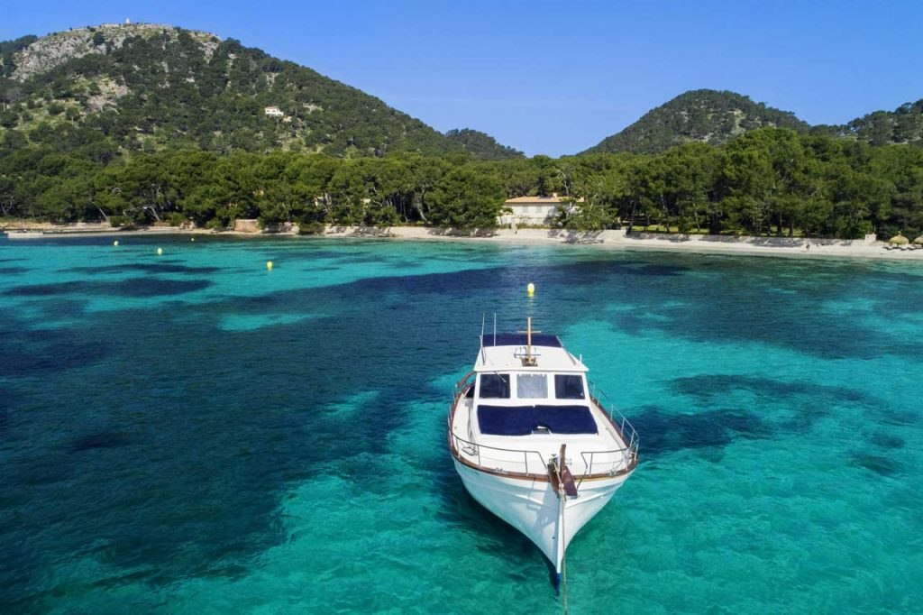 Llaüt-boat in turquoise water with coastline and Tramuntana mountains in the background