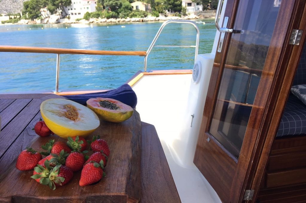 delicious-looking fruits on a boat with bue water and coastline in the background