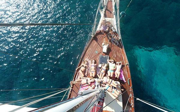 people sunbathing on deck of a sailing yacht
